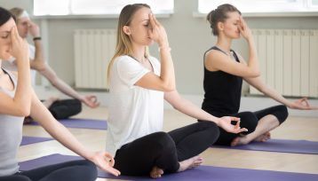 Group of young people in nadi shodhana pranayama pose